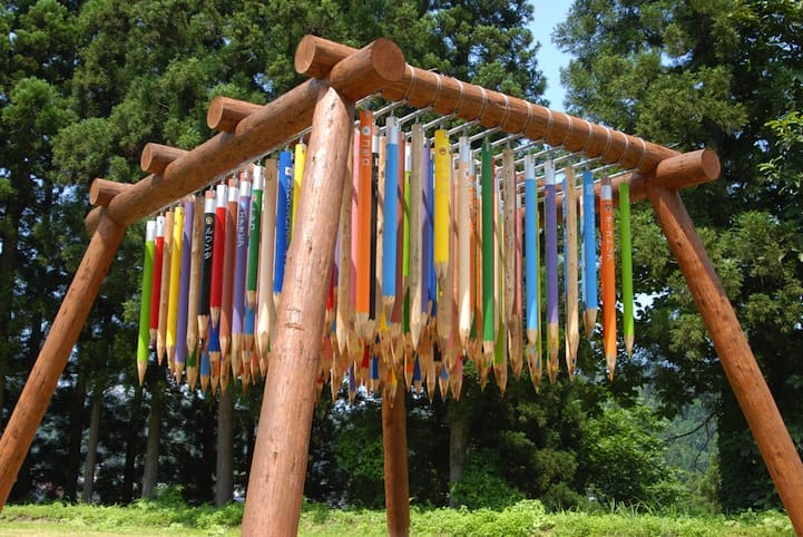 "In the middle of Echigo-Tsumari Art Field in Japan Pascale Marthine Tayou created ""Reverse City"" where enormous colored pencils hewn from trees dangle 2 meters above the ground, pointing down at the visitors below."